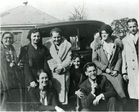 Black and white photo of people standing beside a car